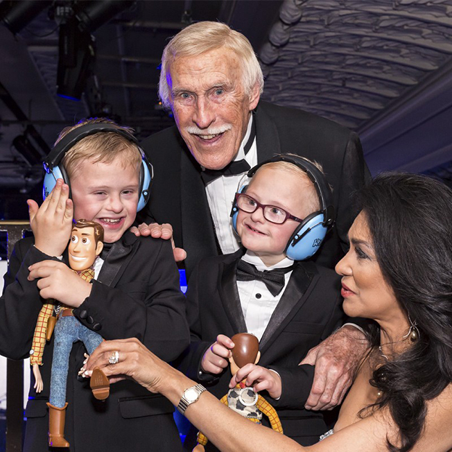 Bruce Forsyth with two young boys playing with toys