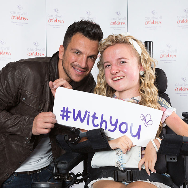 """Peter Andre with young girl holding sign reading """"#Withyou"""""""