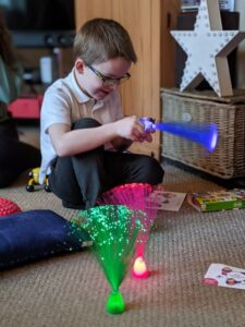 A boy playing with Caudwell Children Get Sensory Packs Fibre Optic Lamps